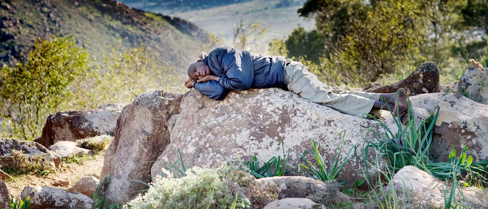 Een migrant uit Ivoorkust in het bos op de berg Gourougou, uitkijkend op de grensovergang met Melilla. Foto: Piet den Blanken/Hollandse Hoogte