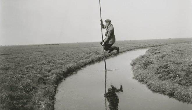Man springt met een polsstok over de sloot met kievitseieren in zijn pet, 1952. Foto: Ben van Meerendonk/IISG