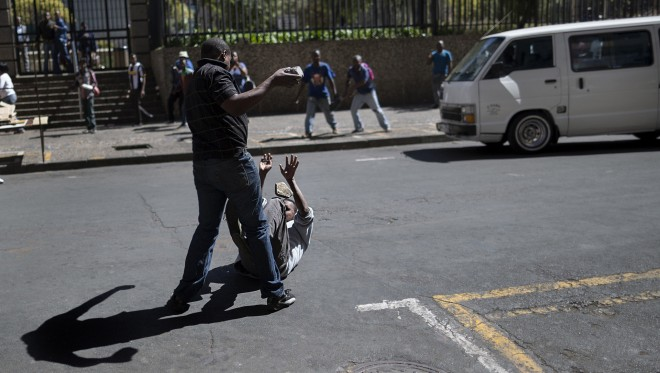 Een locale taxichauffeur valt een man van buitenlandse afkomst aan, tijdens rellen tegen buitenlanders in Johannesburg op 15 april jl. Foto: Marco Longari/AFP