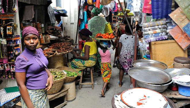 Kinderen werken op de markt van Dantokpa in Cotonou, één van de grootste markten van West-Afrika. Ze zijn een vast onderdeel van het straatbeeld, ook al is arbeid onder veertien jaar illegaal in Benin. Foto: Jan De Deken
