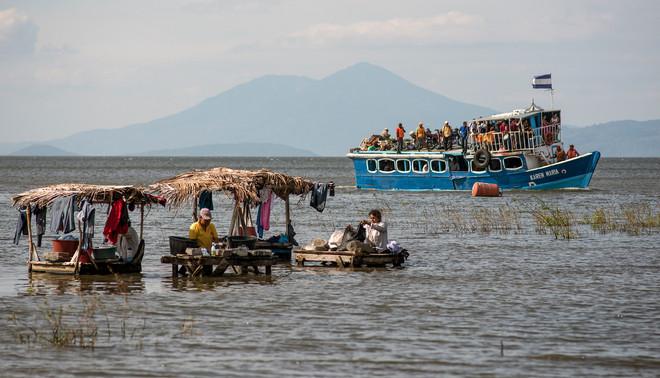 Op de voorgrond wassen lokale bewoners hun kleren in het Nicaraguameer, op de achtergrond vertrekt een passagiersboot richting Ometepe. Foto: Teake Zuidema