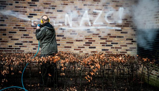 De woorden 'geen azc' worden verwijderd van een muur bij het gemeentehuis in Geldermalsen waar protesten waren tegen een mogelijke azc voor zo'n 1500 vluchtelingen. Foto: Robin Utrecht / Hollandse Hoogte
