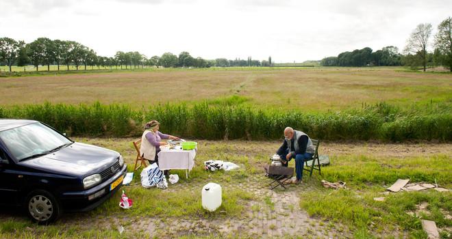 Het recreatiegebied Tuinen van West bij Amsterdam. Een ouder echtpaar geniet van het mooie weer. De man zet thee op een vuurtje en de vrouw maakt kip en kofte klaar. Foto: Mariette Carstens / Hollandse Hoogte