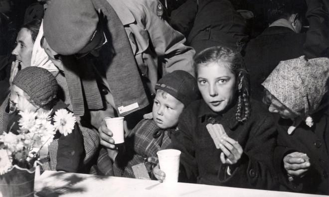 Oktober 1956, bij aankomst in de Jaarbeurshallen in Utrecht krijgen Hongaarse kinderen koekjes en wat te drinken. Foto: Spaarnestad