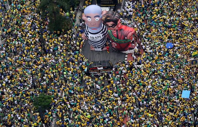 Gigantische inflatables genaamd 'Pixuleco' domineren het straatbeeld tijdens de protesten tegen de benoeming van oud-president Luiz Inacio Lula da Silva door de huidige president Dilma Rousseff (13 maart 2016). Beeld: ANP