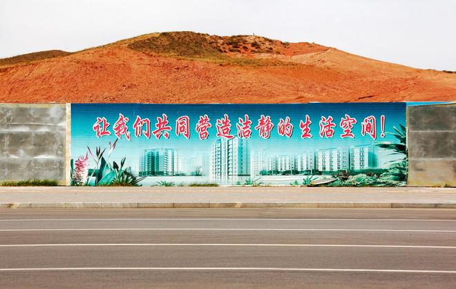 """Een billboard laat de toekomst van de wijk Kangbashi in de stad Ordos mei 2011, China. Ordos ligt in de autonome regio Binnen-Mongolië en laat zich vanuit het Mongools vertalen naar """"paleizen"""" en de stad is gevuld met vers gebouwde flats in pas ontsprongen woonwijken, bedoeld voor arbeiders van de dichtbij gelegen koolmijn. """"Laat ons samen een schone en stille woonomgeving bouwen!"""" is de leus. David Gray / Reuters"""