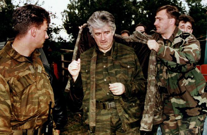Radovan Karadzic wordt door zijn bodyguards in zijn jas geholpen na een televisieoptreden in Pale op 6 september, 1995. Foto: Reuters