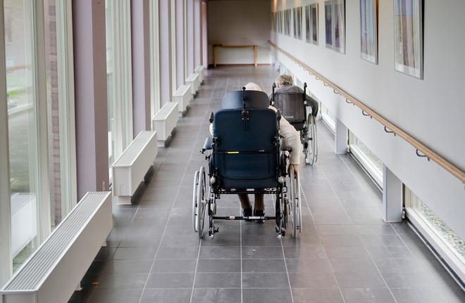 Twee mensen in een rolstoel rijden zichzelf over de afdeling in verzorgingstehuis Vliethoven Delfzijl. Foto: Reyer Boxem / Hollandse Hoogte