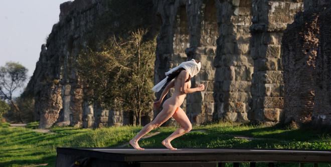 De scène uit de film La Grande Bellezza waarin tijdens een voorstelling een blote kunstenaar tegen een stenen muur aan rent.