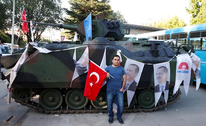 Een man staat voor een tank waar vlaggen aan zijn gehangen van de Turkse president Recep Tayyip Erdogan, voor het parlementsgebouw in Ankara op 16 juli 2016. Foto: Baz / Reuters