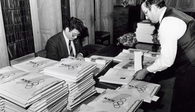 14 april 1986: De Amsterdamse burgemeester Ed van Thijn signeert bidboeken voor de honderd leden van het IOC in het kader van de poging om Amsterdam de Olympische Spelen van 1992 te laten organiseren. Foto: Spaarnestad