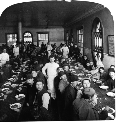 Immigrants seated in the dining hall at Ellis Island, while waiters stand nearby. Photo by Getty