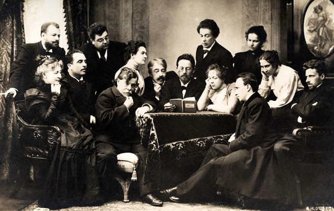 De Russische schrijver Anton Tsjechov leest een theatergezelschap voor. Acteur en regisseur Konstantin Stanislavski leest over Tsjechovs rechterschouder mee (begin twintigste eeuw). Foto: Getty