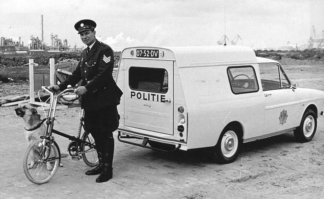 Waarschijnlijk als eerste politieman in Nederland heeft deze agent in 1967 een vouwfiets als dienstuitrusting gekregen.  Wordt het terrein bij het Europoort- en Botlekgebied onbegaanbaar voor de wagen, dan gaat de agent per vouwfiets verder. Foto: ANP