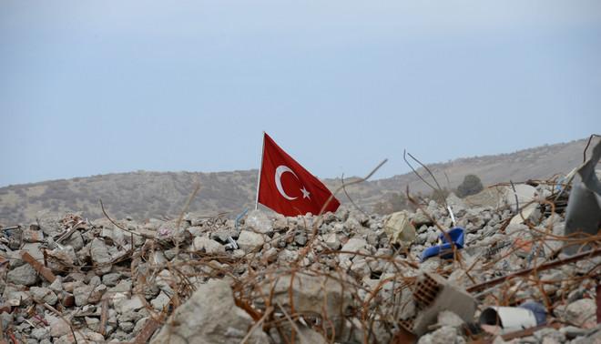 Een Turkse vlag is te zien op het puin dat overbleef na een gevecht tussen het Turkse leger en PKK-strijders. Sirnak, Turkije,14 november 2016. Foto: EPA / STR