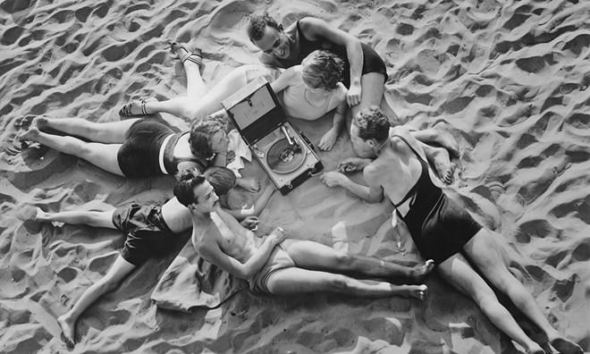 Een groep mensen luistert naar muziek op het strand rond 1930. Foto: FPG / Getty Images