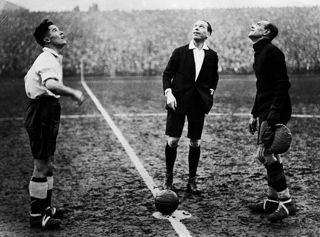 Voor een voetbalwedstrijd in 1931 wordt een muntje in de lucht gegooid. Foto: Getty Images