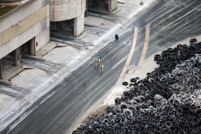 Werknemers fietsen langs een berg banden die als brandstof van een cementfabriek dienen. Duitsland, augustus 2014. Foto: Jasper Juinen / Getty Images
