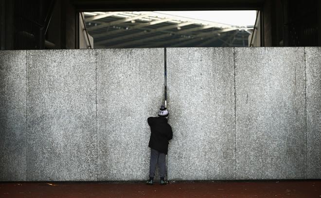 Een jonge Swansea City-supporter spiekt door een kier het stadion in voor de wedstrijd tegen AFC Bournemouth op 31 december 2016. Foto: Jordan Mansfield / Getty Images