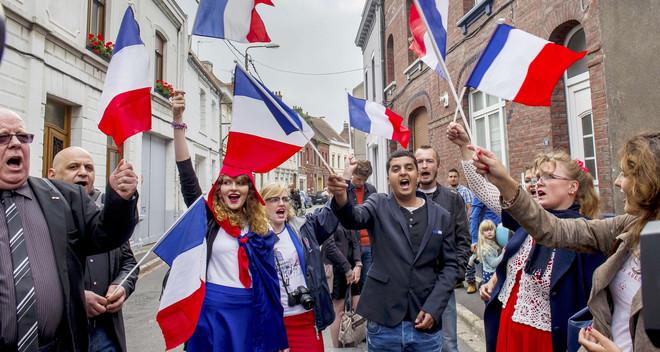 Front National-supporters zwaaien met vlaggen tijdens een vlooienmarkt in Hénin-Beaumont op 14 september, 2014. Foto: Philippe Huguen / AFP
