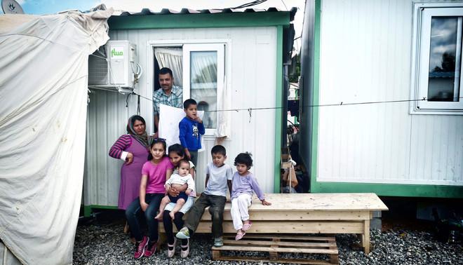 11 mei 2017: Een Afghaanse familie met zes kinderen voor hun eigen container in een vluchtelingenkamp nabij Athene. Foto: Louisa Gouliamaki / AFP