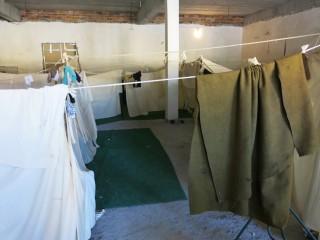 In een van de oude militaire gebouwen rond het kamp hebben gezinnen afscheidingen gemaakt voor wat privacy. Foto: Maite Vermeulen