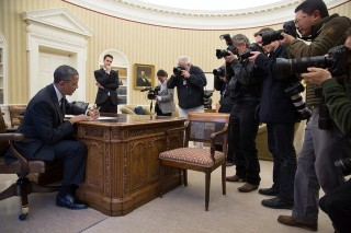'Photojournalists photograph Obama as he signs H.R. 2747: Streamlining Claims for Federal Contractor Employees Act, and S. 893: The Veterans' Compensation Cost-of-Living Adjustments Act of 2013, Nov. 21, 2013.' Foto: Pete Souza/the White House