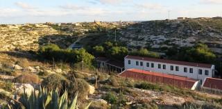 Op de voorgrond het detentiecentrum waar bootvluchtelingen hun asielprocedure afwachten, daarachter het stadje van Lampedusa. Foto: Maite Vermeulen