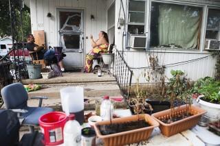 Mike en Desiree rokend op de veranda voor hun huis. Waarschijnlijk moeten ze binnenkort uit het huis vertrekken omdat ze de rekeningen niet meer kunnen betalen. Foto: Barbara Doux/Hollandse Hoogte
