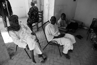 'In het hotel met politie zitten vier mannen op ijzeren stoelen en een groen veldbed.' Foto: Andreas Stahl