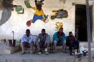 Mannen in Timboektoe voor een fotozaak. Op de muur achter hen enkele stripfiguren waarvan de gezichten door de islamisten met zwarte verf zijn weggevaagd. Foto: Andreas Stahl
