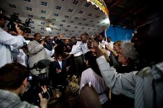 De Oegandese parlementariër David Bahati, die de anti-homowet opstelde, wordt gezegend onder leiding van Martin Ssempa, de bekendste predikant van Oeganda. Foto: Hollandse Hoogte