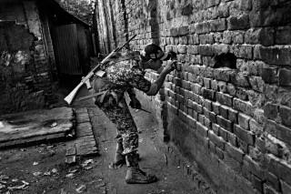 Een soldaat van de Indian Border Security Force (BSF) gluurt door een gat in de muur in de grensstad Hili (India) om te kijken of mensen illegaal over de grensmuur klimmen. Foto: Gaël Turine/HH