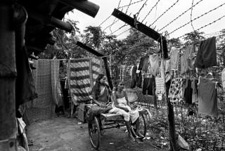 Een meisje verzorgt haar oma in de tuin van het huis waar de hele familie woont, in de Krishnaganj regio (India). Hun huis stond er al voor het grenshek werden geplaatst. Foto: Gaël Turine/HH