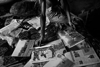 Nour Islan (45) toont foto's uit de krant waarop te zien is hoe zijn dochter Fellani (14) werd neergeschoten. Zij probeerde samen met haar vader 's nachts naar Bangladesh te komen om haar toekomstige man te ontmoeten. Foto: Gaël Turine/HH
