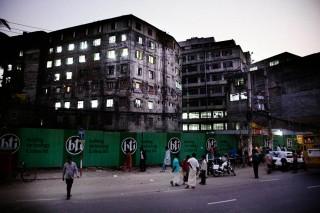 Dhaka in de avond. Achter de ramen waar nog licht brandt zijn de werknemers van de textielfabriek nog aan het werk. Foto: Pieter van den Boogert