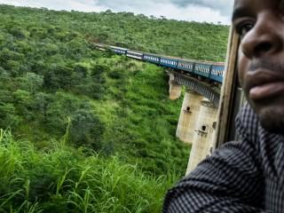 Een passagier kijkt naar buiten terwijl de trein over een brug rijdt. In totaal zijn er ongeveer driehonderd bruggen op de route. Foto: Sean van der Steen
