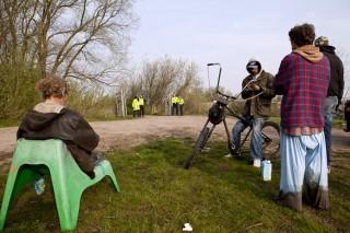 Bewoners die al van 't Landje zijn verwijderd, kijken toe. Foto: Lege Fles