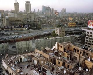 Een groep mensen woont op de bovenste verdieping van woonhuizen, achter de billboard op de Zes Oktober ring in Caïro. Foto: Mark Nozeman