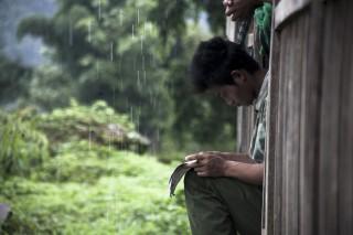Een KIA-soldaat leest de krant, naast hem regent het. Grenspost in Kachin, Birma. Foto's: Andreas Stahl