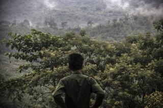 Een KIA-soldaat kijkt naar de grenspost aan de andere kant van de vallei, waar het Birmese leger is gestationeerd.