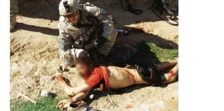 Een Amerikaanse soldaat poseerde in januari 2010 bij het lichaam van een Afghaanse jongen die een paar minuten daarvoor is neergeschoten.