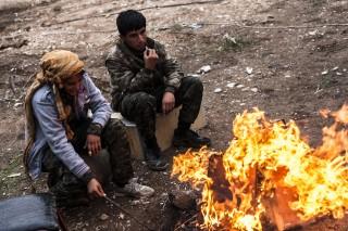 Een Arabische YPJ strijdster en een Koerdische YPG strijder bij een checkpoint aan het front in Rabia, grens Irak-Syrië. Foto: Andreas Stahl