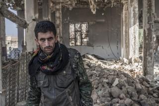 Een YPG-strijder in de moskee van Tel Marouf, Syrië. Foto: Andreas Stahl