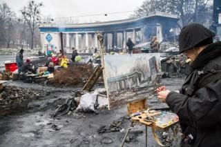 18 februari 2014: De Oekraïense kunstenaar Sergey Pushchenko schildert de barricades van het Maidanplein. Foto: Guy Corbishley/Hollandse Hoogte