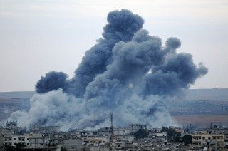 12 december 2014: Rookwolken boven de Syrische stad Kobani gezien vanaf de Turkse grens. Dat het IS maar niet lukt deze stad te veroveren, zou kunnen bewijzen dat ze hun momentum aan het verliezen zijn. Foto: Binnur Ege Gurun/Getty