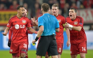 Spelers van Bayer 04 Leverkusen doen hun beklag bij de scheidsrechter tijdens de wedstrijd tegen Atletico de Madrid. 25 februari 2015. Foto: Martin Meissner/HH
