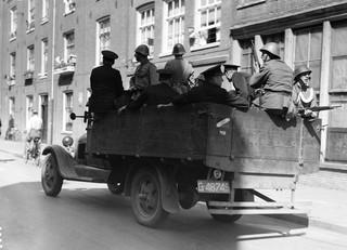 7 juli 1934: Surveillancewagen van de politie met agenten en militairen, tijdens rellen in de Jordaan tegen verlaging van de werkeloosheidsuitkeringen. Vijf mensen kwamen bij deze rellen om het leven. Foto: ANP