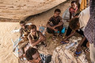 Million Ishta (midden) en zijn Ethiopische reisgenoten op het strand in Obock, Djibouti.