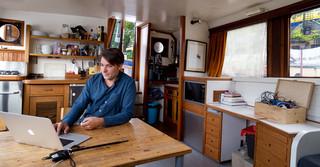 Hannes Mühleisen in de woonkamer van zijn woonboot, vlak bij station Amsterdam Centraal. Foto: Rob Wetzer